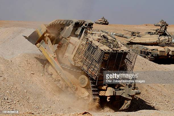An Israel Defense Force armoured Caterpillar D-9 clearing the way for Mark IV main battle tank during an exercise.