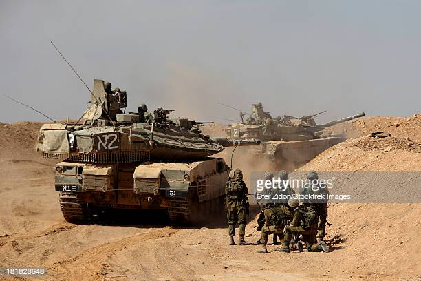 An Israel Defense Force Merkava Mark IV main battle tank exercise with infantry forces.