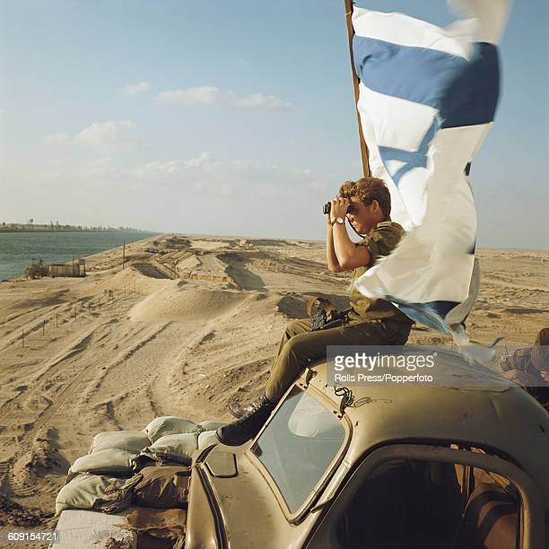 An Israel Defense Force soldier uses a pair of binoculars to view activity on the Egyptian side of the Suez Canal from the roof of a truck on the...