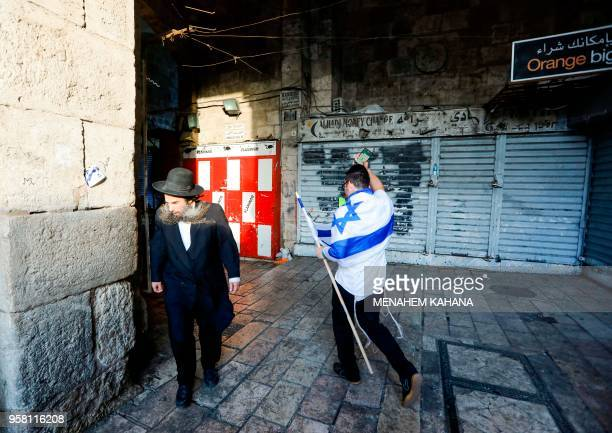An Israel draped in his national flag and holding another walks past an UltraOrthodox Jewish man in the old city of Jerusalem on May 13 as Israelis...