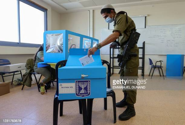 An Israel soldier casts his early vote for the country's upcoming legislative elections, at the Golani military base in Kafr Qara near Haifa, on...