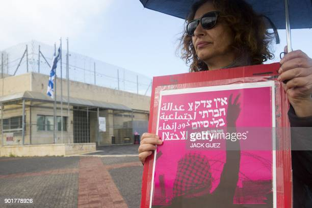 An Israeli activist holds a placard reading in Arabic and Hebrew 'No social justice without the end of the occupation' during a protest calling for...