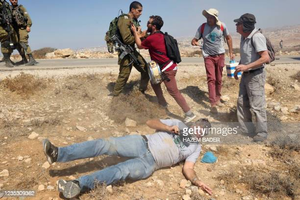 An Israeli activist lies injured on the floor after he was pushed by an Israeli soldier during a demonstration against Israeli land confiscation and...