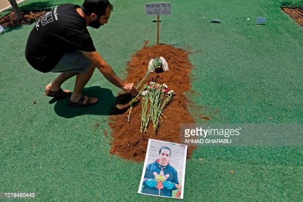 An Israeli activist places flowers on a symbolic grave along Rothschild boulevard in Israel's Mediterranean coastal city of Tel Aviv on June 12, 2020...