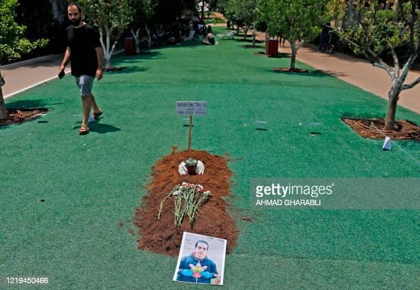 An Israeli activist walks near a symbolic grave along Rothschild boulevard in Israel's Mediterranean coastal city of Tel Aviv on June 12, 2020 in...