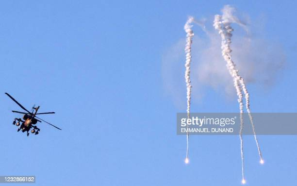 An Israeli AH-64 Apache attack helicopter releases flares near Sderot, in southern Israel on the border with the Hamas-controlled Gaza Strip, on May...