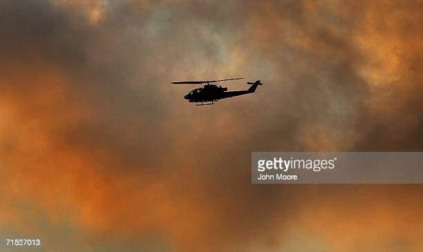 An Israeli Apache attack helicopter passes by as Israelis take part in a meditation and prayer session on the beach July 27, 2006 in Tel Aviv,...