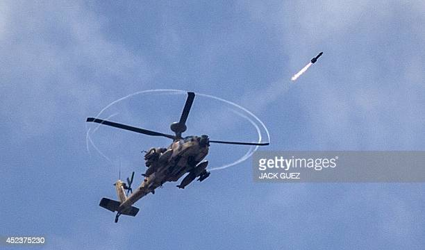 An Israeli Apache attack helicopter shoots a missile over the Gaza Strip as seen from Israel's border with Gaza on July 19 2014 Israeli strikes...