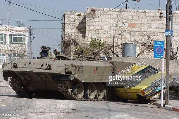 An Israeli APC smashes a Palestinian Taxi in the West Bank city of Ramallah Wednesday March 12 2002