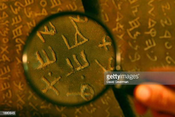 An Israeli archaeologist reviews the inscription on the Jehoash tablet in the storerooms of the Israeli Antiquities Authority March 27 2003 in...
