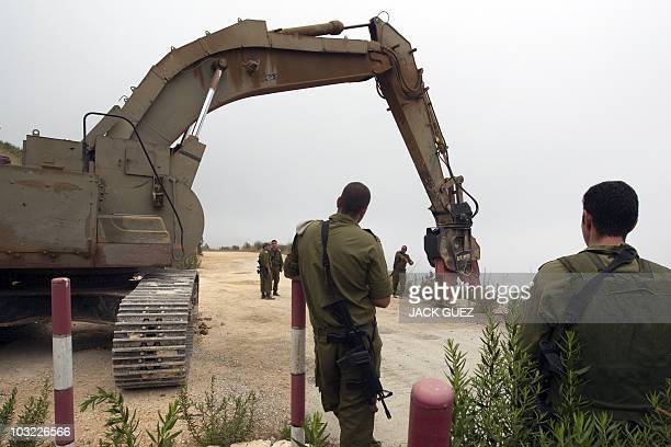 An Israeli army bulldozer prepares to return to the same place where it was working the previous day when clashes between Israeli and Lebanese troops...