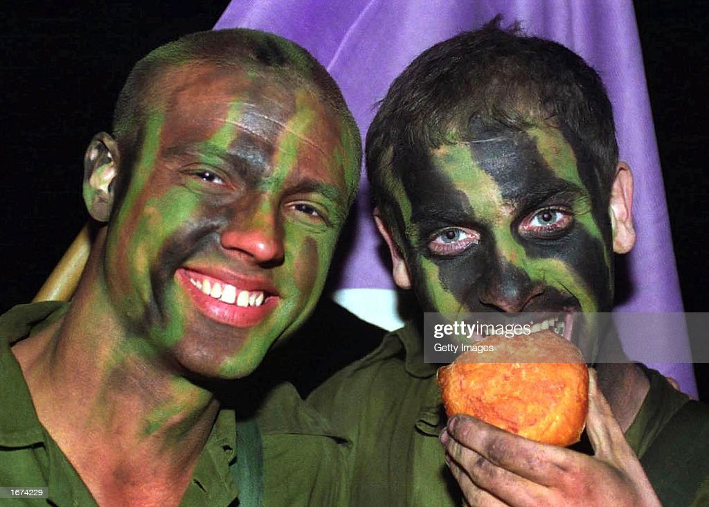 An Israeli army conscript bites into a jelly donut after he and his comrades completed a 37.5 mile forced march to mark the end of basic training and the formal acceptance to the Givati infantry brigade December 5, 2002 at an army base in southern Israel. Filled donuts are traditional food during the current eight-day Jewish festival of Hanukkah, which commemorates the Jewish uprising in the second century B.C. against the Greek-Syrian kingdom, which had desecrated the Jewish Temple in Jerusalem.