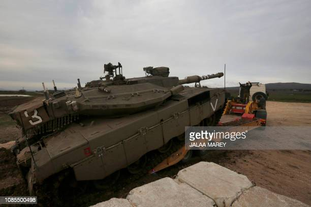 An Israeli army Merkava tank is loaded into a truck in the Israeliannexed Golan Heights on January 20 2019 Israel's military said its air defence...