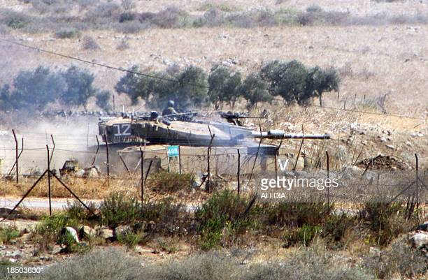 An Israeli army Merkava tank is pictured from the Lebanese side of the border near the Wazzani river during maneuvres by Israeli forces in northern...