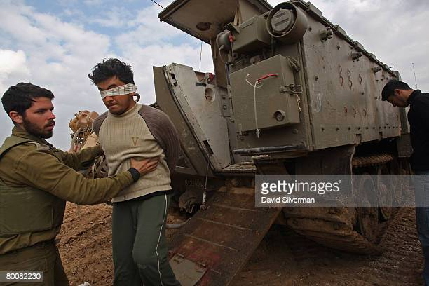 An Israeli army officer helps a blindfolded Palestinian prisoner who was captured in fighting with Palestinian militants step out of an Armored...