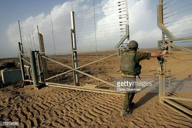 An Israeli army officer opens a gate in the border fence to allow a column of tanks and armored bulldozers to advance into the Gaza Strip to operate...