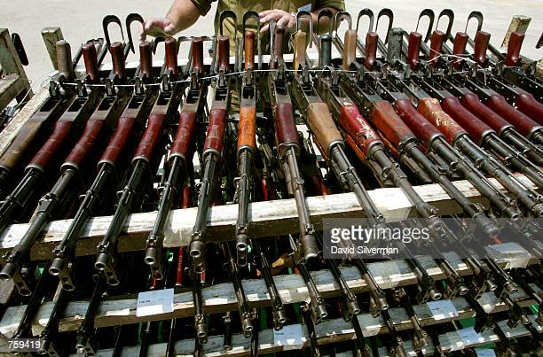 An Israeli army officer stands behind rows of AK47 assault rifles on display at an army base April 10 2002 near the central Israeli town of Ramle The...