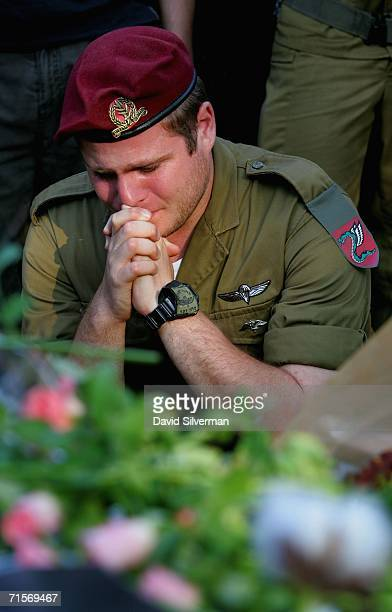An Israeli army paratrooper mourns at the wreathcovered grave of his friend and commander Lieutenant Ilan Gabay during Gabay's funeral August 2 2006...