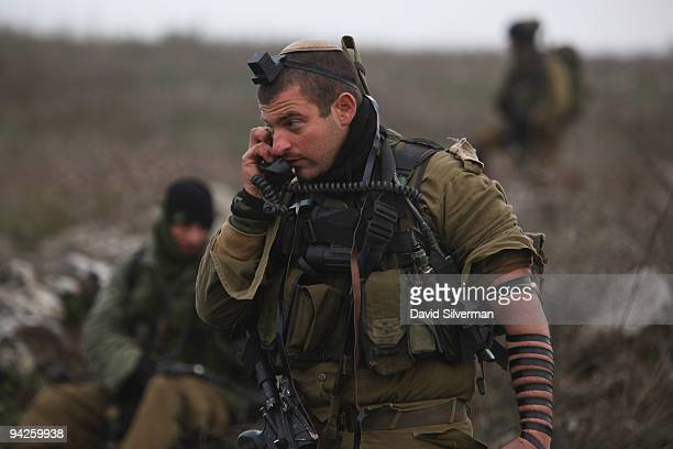 An Israeli army paratrooper officer pauses during his morning prayers to give orders on his field radio during a livefire training exercise December...