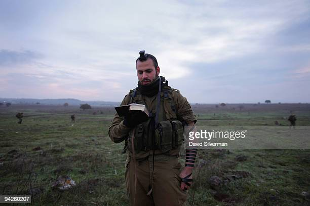 An Israeli army paratrooper recites his morning prayers before joining his comrades in a livefire training exercise December 10 2009 on the Golan...