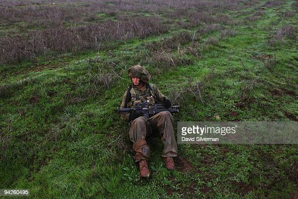 An Israeli army paratrooper rests at the first opportunity during a livefire training exercise December 10 2009 on the Golan Heights The Israeli...