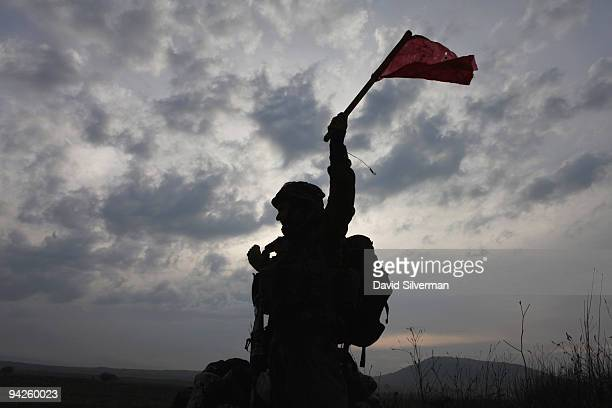 An Israeli army paratrooper signals the advance during a livefire training exercise December 10 2009 on the Golan Heights The Israeli Knesset...