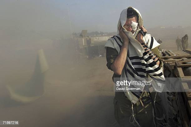 An Israeli army reservist recites his morning prayers wrapped in a prayer shawl and phylacteries amongst the dust kicked up by his artillery unit as...