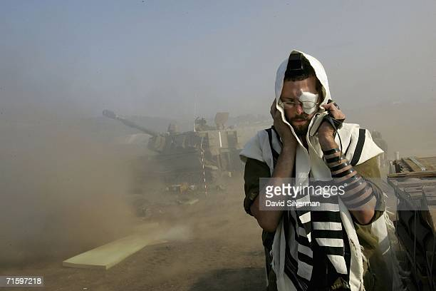 An Israeli army reservist recites his morning prayers wrapped in a prayer shawl and phylacteries as his artillery unit opens fire against Hezbollah...
