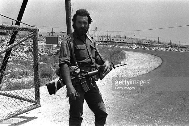 An Israeli army reservist stands guard July 25 1980 at the entrance to the West Bank settlement of Ariel Established in 1978 this settlement is today...