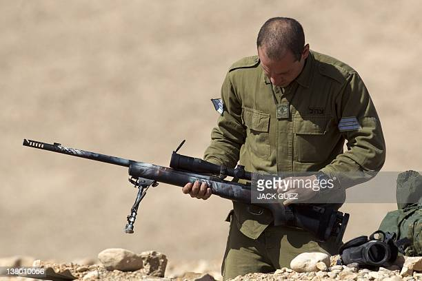 An Israeli army sniper cleans his gun after an exercise at the Shizafon army base in the Negev Desert north of the southern city of Eilat on January...