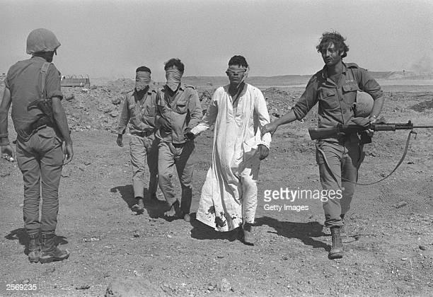 An Israeli army soldier leads blindfolded Egyptian prisonersofwar October 21 1973 in the Sinai Desert during the Yom Kippur War Israeli Prime...