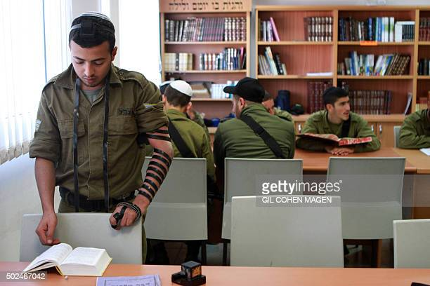 SMITH An Israeli army soldier of the Shachar Kachol UltraOrthodox Jewish unit pray at a synagogue on December 21 2015 at the Nevatim Air force base...