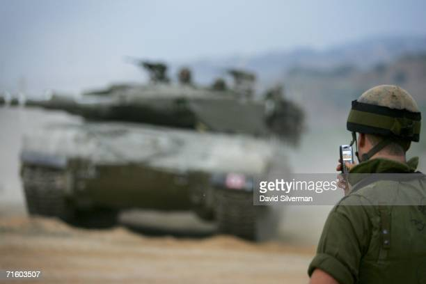An Israeli army soldier uses his 3rd generation mobile phone to make a video clip of an approaching Merkeva tank inside Lebanon on August 8 2006 at a...