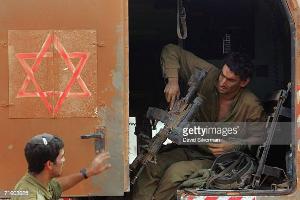 An Israeli army soldier who was lightly wounded combating Hezbollah militia in south Lebanon passes his assault rile to a medic as he waits to be...