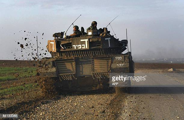 An Israeli army tank patrols the border with the Gaza Strip on December 29 2008 Israeli tanks massed at the Gaza border today as warplanes continued...