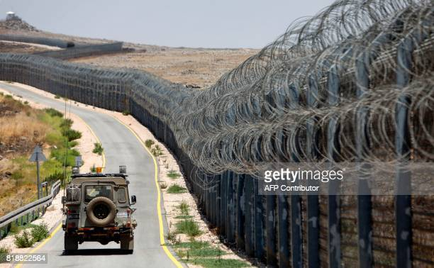 An Israeli army vehicle is seen driving along the road parallel to the border fence separating the Israeli-annexed Golan Heights and Syria, on July...