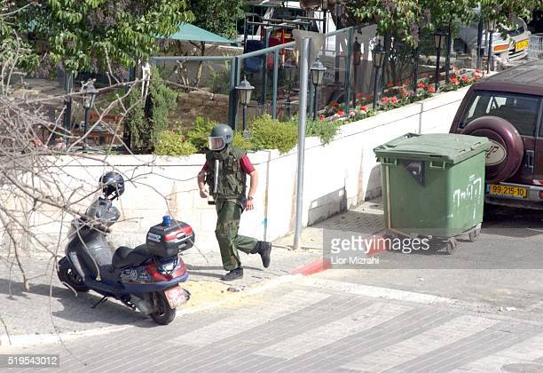 An Israeli bomb squad police officer examines a suspicious bag in Jerusalem Thursday March 07 2002 A Palestinian suicide bomber was caught as he was...
