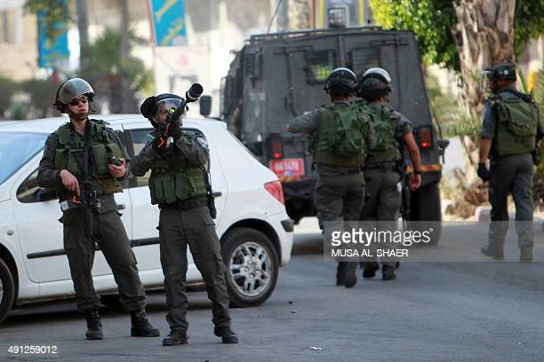 An Israeli border guard aims his weapon at Palestinians during clashes in Abu Dis on the outskirts of east Jerusalem on October 4 as tensions mounted...
