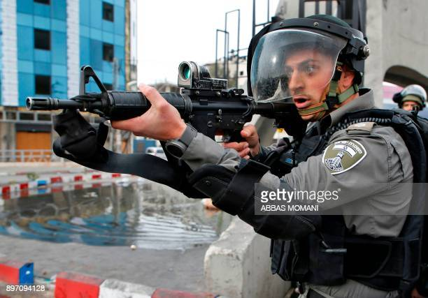 TOPSHOT An Israeli border guard aims his weapon during clashes with Palestinian protesters north of Ramallah in the Israeli occupied West Bank on...