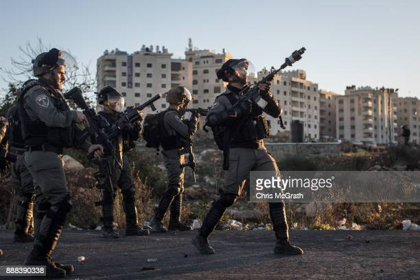 An Israeli border guard fires tear gas at Palestinian protesters during clashes near an Israeli checkpoint on December 8 2017 in Ramallah West Bank...