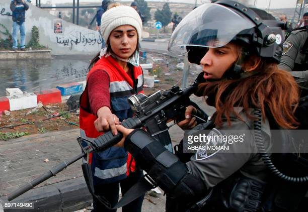 TOPSHOT An Israeli border guard is confronted by a Palestinian protester during clashes north of Ramallah near the Israeli settlement of Beit El in...