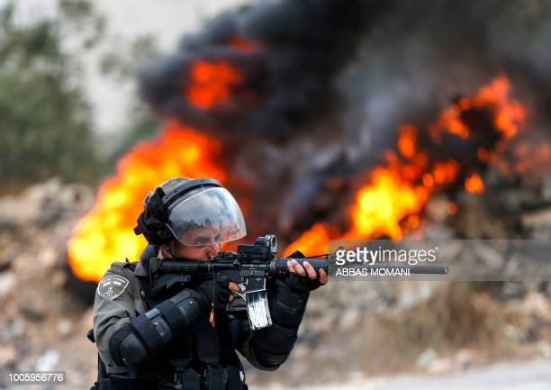 An Israeli border guard looks through the scope of his rifle during clashes with Palestinian protesters in the village of Kobar west of Ramallah in...