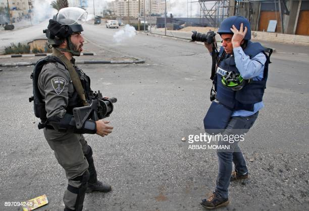 An Israeli border guard reacts in front of a photojournalist during clashes with Palestinian protesters north of Ramallah in the Israeli occupied...