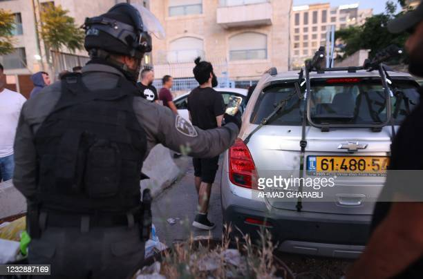 An Israeli border guard takes a picture of a bullet hole in a car in the east Jerusalem neighbourhood of Sheikh Jarrah on May 14 following clashes...