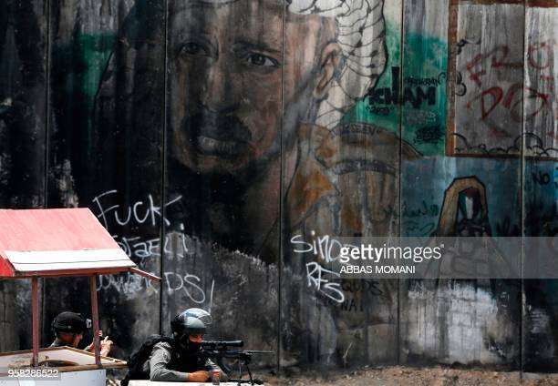 TOPSHOT An Israeli border guard takes a picture of another guard in Ramallah in the occupied West Bank on May 14 as Palestinians protest over the...