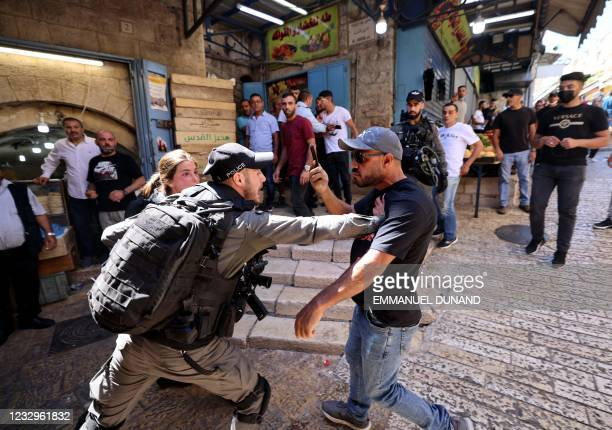 An Israeli border police member confronts a Palestinian man during protests against Israel's occupation and its air campaign on the Gaza strip, at...
