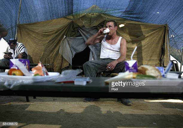An Israeli border police officer has breakfast as another prays in the Reim army base on August 19 2005 in the southern Gaza Strip As Israel's...