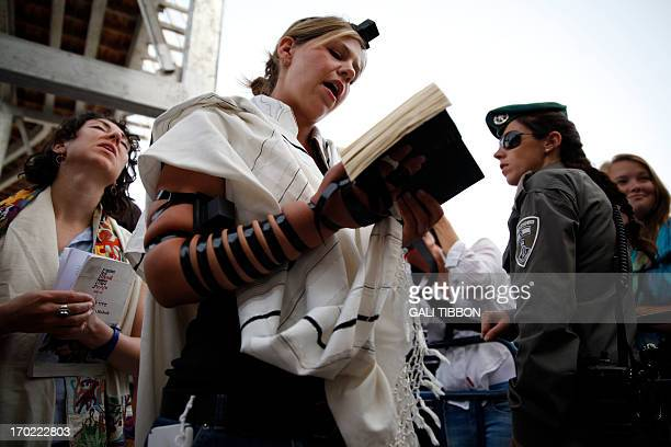 An Israeli Border Police woman stands guard near members of the liberal Jewish religious group Women of the Wall wearing phylacteries and the Tallit...