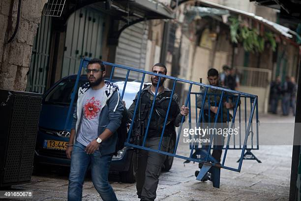An Israeli border policeman caries a barrier next to a stabbing scene on October 7 2015 in Jerusalem's Old City Israel According to Israeli police a...
