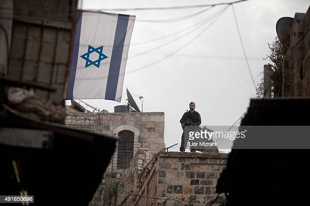 An Israeli border policeman stands on a roof next to a stabbing scene on October 7 2015 in Jerusalem's Old City Israel According to Israeli police a...
